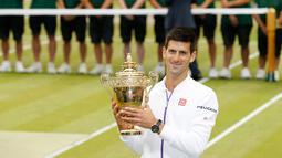 Petenis Serbia, Novak Djokovic menunjukkan trofi kemenangannya setelah mengalahkan petenis Swiss, Roger Federer di babak final tunggal putra Wimbledon 2015, London, Minggu (12/7). Ini adalah gelar Wimbledon ketiga bagi Djokovic.  (REUTERS/Stefan Wermuth)