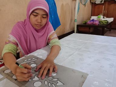 Pengrajin melukis motif sasirangan yang diinginkan di atas kain ukuran 2 meter menggunakan kain katun dan sutera di daerah Sasiranga, Banjarmasin, Kalimantan Selatan (16/1/2017). (Liputan6.com/Novi Nadya)