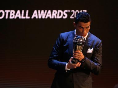 Bintang Real Madrid, Cristiano Ronaldo meraih penghargaan pemain terbaik dalam acara The Best FIFA Football Awards 2017 di London, Senin (23/10). Ronaldo sukses mempertahankan gelar The Best FIFA Men's Player yang diraihnya tahun lalu. (AP/Alastair Grant)