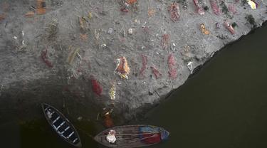 Kuburan dangkal di pasir, beberapa di antaranya diduga orang yang meninggal karena virus corona COVID-19, terlihat dekat tempat kremasi di tepi Sungai Gangga, Phafamau, Allahabad, India, Sabtu (5/6/2021). (SANJAY KANOJIA/AFP)