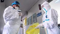 Petugas laboratorium melepaskan pakaian pelindung di sebuah laboratorium di Shenyang, provinsi Liaoning timur laut China, Rabu (12/2/2020). WHO kini tidak lagi menyebut virus yang merebak di China sebagai Virus Corona Baru. (STR/AFP)