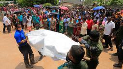 Anggota militer Sri Lanka mengangkut jenazah korban tewas akibat tertimbun sampah longsor di Meetotamulla, dekat ibukota Kolombo, Minggu (16/4). Timbunan sampah mencapai 91 meter menghantam ratusan rumah warga di bawahnya. (AP Photo/Eranga Jayawardena)
