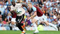 Striker Manchester United, Romelu Lukaku, beradu cepat dengan bek Burnley, Ben Mee, pada laga Premier League di Stadion Turf Moor, Burnley, Minggu (2/8/2018). Burnley kalah 0-2 dari MU. (AFP/Lindsey Parnaby)