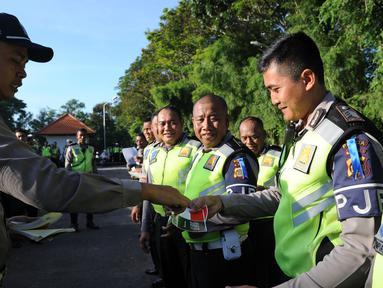 Petugas Polisi memberikan stiker bergambar bendera Indonesia dan Arab Saudi kepada rekannya selama persiapan menyambut kedatangan Raja Arab Saudi Salman bin Abdulaziz di Nusa Dua, Bali (2/3). (AFP Photo / Sonny Tumbelaka)