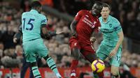 Penyerang Liverpool, Sadio Mane berebut bola dengan pemain Arsenal, Ainsley Maitland-Niles pada lanjutan Liga Inggris di Anfield Stadium (29/12). Kemenangan ini, membuat Liverpool  kokok di puncak klasemen dengan poin 54. (AP Photo/Rui Vieira)