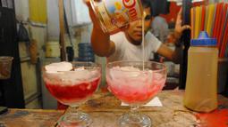 Es pocong adalah bubur sumsum yang dicampur dengan potongan pisang tanduk, diberi es batu dan di atasnya disiram sirup berwarna merah muda, Depok, Kamis (3/7/14). (Liputan6.com/Miftahul Hayat)