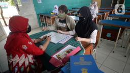Guru Wali Kelas berdiskusi dengan wali murid saat pembagian raport di SMP Negeri 18 Tangerang Selatan, Banten, Kamis (17/12/2020). Pembagian raport diketahui sedang dilaksanakan sejumlah sekolah.  (merdeka.com/Dwi Narwoko)