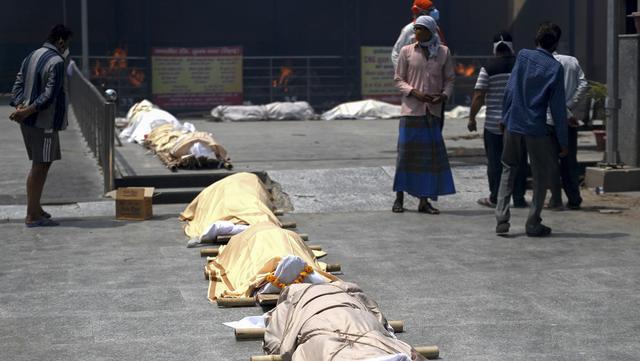 Warga berdiri dekat jasad korban virus corona COVID-19 yang akan dikremasi di tempat kremasi di New Delhi, India, Rabu (28/4/2021). Korban tewas akibat COVID-19 yang terus berjatuhan membuat jasad korban harus antre untuk dikremasi. (Money SHARMA/AFP)