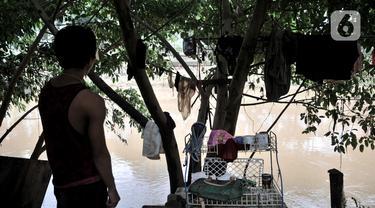 Salah seorang warga berdiri di pinggir bantaran kali usai banjir merendam gubuk miliknya yang berada di pinggir Kanal Banjir Barat (KBB), Jakarta, Rabu (8/1/2020). (merdeka.com/Iqbal S Nugroho)