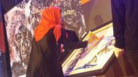 Calon Wakil Gubernur Jawa Timur Puti Guntur Soekarno melukis di atas kanvas putih (Liputan6.com/Dian Kurniawan)