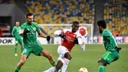 Aksi penyerang muda Arsenal, Eddie Nketiah melewati dua pemain Vorskla pada laga lanjutan Grup E Liga Europa yang berlangsung stadion NSK Olimpiyskiy, Kyiv, Jumat (30/11). Arsenal menang atas Vorskla 3-0. (AFP/Sergei Supinsky)
