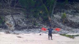 Seorang pria melambaikan jaket penyelamat saat meminta pertolongan ketika terdampar di Pulau Faradik, Mikronesia, 7 April 2016. Tiga orang pelaut terdampar setelah kapal yang mereka tumpangi tersapu ombak setinggi dua meter. (ENSIGN JOHN KNIGHT/NMCO/AFP)