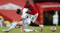 Pemain Manchester United, Paul Pogba, berebut bola dengan pemain West Ham United, Declan Rice, pada laga Premier League di Stadion Old Trafford, Rabu (22/7/2020). Kedua tim bermain imbang 1-1. (Clive Brunskill/Pool via AP)