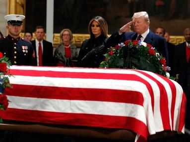 Presiden AS Donald Trump dan Melania Trump memberikan penghormatan terakhir kepada George HW Bush di Gedung Capitol, Washington, Senin (3/12). Jenazah Presiden ke-41 AS itu disemayamkan di Rotunda Capitol Hill selama beberapa hari. (AP/Jacquelyn Martin)