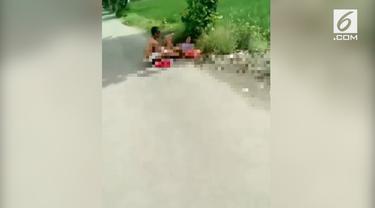 Seorang pengendara motor merekam adegan dua orang yang sedang berhubungan intim di pinggir jalan. Diduga pelakunya alami gangguan kejiwaan.