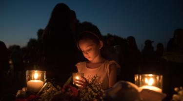 Lucretia Martinez (7) menyalakan lilin untuk mengenang korban penembakan di sekolah Santa Fe, Texas, Amerika serikat, Jumat (18/5). Sebanyak 10 orang tewas dalam tragedi penembakan tersebut. (AFP)