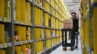 Seorang pekerja mencari barang pesanan milik pelanggan di pusat gudang toko online Amazon usai resmi dibuka di Singapura, Kamis (27/7). Perusahaan yang berdiri sejak 1995 itu kini telah hadir di kawasan Asia Tenggara. (AP Photo/Joseph Nair)