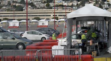 Mobil-mobil menunggu untuk mendapatkan vaksin COVID-19 di pusat vaksinasi drive-thru di City College of San Francisco di San Francisco, Senin (1/2/2021). Ketika pasokan vaksin COVID-19 meningkat, UC San Francisco memperluas upaya vaksinasi kepada mereka yang paling berisiko. (AP Photo/Jeff Chiu)