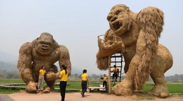 Para siswa berfoto dengan patung King Kong raksasa yang terbuat dari jerami di Huay Teung Tao Lake, Don Kaeo, Chiang Mai, Thailand, Rabu (3/4). Tempat ini merupakan satu dari banyak spot foto instagramable di Chiang Mai. (Lillian SUWANRUMPHA/AFP)