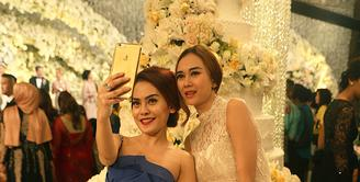 Resepsi pernikahan Nabila Syakieb dan Reshwara Argya Radinal turut dihadiri oleh deretan selebriti tanah air. Seperti Aura Kasih yang datang bersama temannya, ia tampak cantik mengenakan gaun putih panjang. (Fathan Rangkuti/Bintang.com)