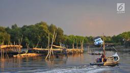 Nelayan melintasi area permukaan air laut yang menyurut di sekitar pesisir Kamal Muara, Jakarta, Kamis (15/3). Fenomena turunnya permukaan air di daerah ini semakin menyulitkan akses nelayan untuk pergi melaut. (Merdeka.com/Iqbal S Nugroho)