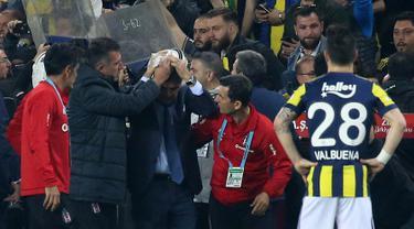 Pelatih Besiktas, Senol Gunes memegangi kepalanya setelah terkena lemparan benda tajam dari tribun penonton pada semifinal Piala Turki melawan Fenerbahce di Istanbul, Kamis (19/4). Insiden di menit ke-58  ini membuat pertandingan terpaksa ditunda. (AFP)