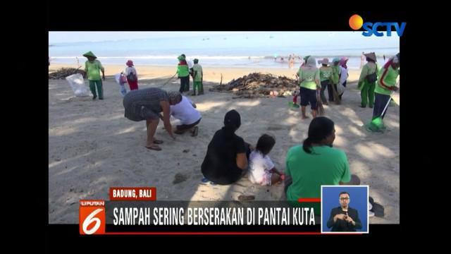 Warga dibantu wisatawan asing bersihkan Pantai Kuta, Bali, dari tumpukan sampah.