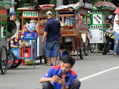 Pedagang kaki lima menjajakan makanan dan minuman di sisi jalan sekitar kawasan Patung Kuda Jakarta, Rabu (5/1/2019). Mereka mencoba peruntungan saat para buruh melakukan aksi perayaan Hari Buruh International atau May Day. (Liputan6.com/Helmi Fithriansyah)