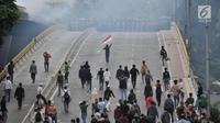 Pelajar berhadap-hadapan dengan barikade polisi saat berdemonstrasi di Jalan Layang Slipi, Petamburan, Jakarta, Rabu (25/9/2019). Bentrok pelajar dengan polisi yang terjadi sejak siang hingga malam tersebut dipicu kekerasan yang dialami pelajar saat demo di Gedung DPR. (merdeka.com/Iqbal Nugroho)