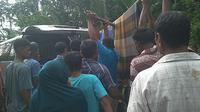 Warga memapah jenazah diduga korban penyerangan babi hutan (Liputan6.com/Ist)