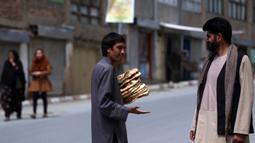 Seorang pria membawa roti gratis dari kota selama lockdown untuk mencegah penyebaran virus corona, pada bulan suci Ramadan di Kabul, Afghanistan (4/5/2020). Muslim di seluruh dunia sedang menjalankan Ramadan, ketika mereka menahan diri dari makan, minum dari subuh hingga senja. (AP/Rahmat Gul)