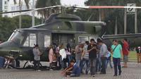 Warga mengerumuni helikopter TNI di kawasan Monumen Nasional, Jakarta, Jumat (19/4). Libur panjang perayaan Paskah 2019 dimanfaatkan warga untuk berwisata di kawasan Monumen Nasional. (Liputan6.com/Helmi Fithriansyah)