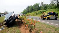 Petugas saat akan mengevakuasi mobil Innova yang terbalik di KM 208 Tol Palikanci (Palimanan-Kanci), Jawa Barat, Rabu (21/6). Tak ada korban jiwa dalam kecelakaan yang diduga karena sopir mobil B 2247 TKL itu mengantuk. (Liputan6.com/Gempur M Surya)