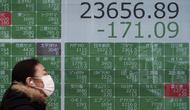 Seorang wanita berjalan melewati layar monitor yang menunjukkan indeks bursa saham Nikkei 225 Jepang dan lainnya di sebuah perusahaan sekuritas di Tokyo, Senin (10/2/2020). Pasar saham Asia turun pada Senin setelah China melaporkan kenaikan dalam kasus wabah virus corona. (AP Photo/Eugene Hoshiko)