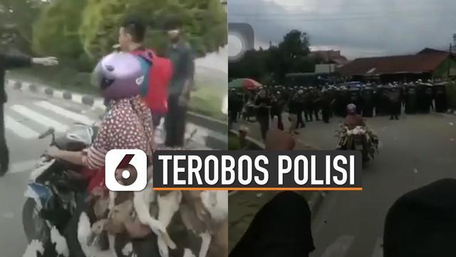 Seorang emak-emak menggunakan motor membawa banyak bebek dibantu oleh para mahasiswa untuk melewati barikade polisi.