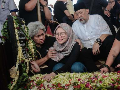 Komedian Indro Warkop bersama anak-anaknya menangis di pusara sang istri Nita Octobijanthy di TPU Tanah Kusir, Jakarta, Rabu (10/10). Nita meninggal karena sakit kanker paru-paru yang dideritanya. (Liputan6.com/Faizal Fanani)
