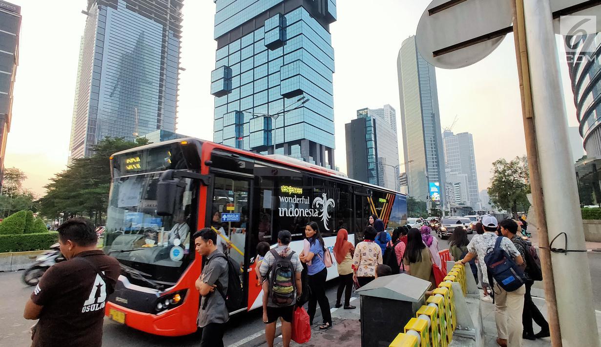 Warga menaiki angkutan umum di tepi Jalan Jenderal Sudirman, Jakarta, Senin (8/7/2019). Tidak adanya halte menyebabkan warga terpaksa menunggu angkutan umum di tempat seadanya. (Liputan6.com/Immanuel Antonius)