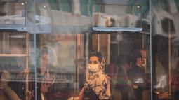 Seorang wanita dengan masker menaiki bus di pusat Kota Teheran, 28 Juni 2020. Presiden Iran Hassan Rouhani pada Minggu (28/6) mengatakan mengenakan masker di tempat umum akan menjadi wajib mulai pekan depan di tengah meningkatnya kasus dan kematian akibat COVID-19. (Xinhua/Ahmad Halabisaz)