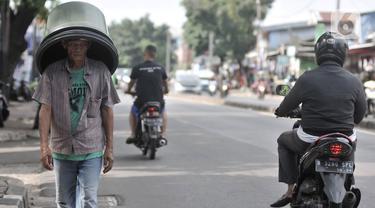 Pedagang tanpa mengenakan masker saat melintas di kawasan Pasar Minggu, Jakarta, Rabu (8/4/2020). Organisasi Kesehatan Dunia (WHO) telah merekomendasikan agar siapa saja menggunakan masker saat berada di tempat umum demi memutus mata rantai penyebaran virus Corona. (merdeka.com/Iqbal Nugroho)