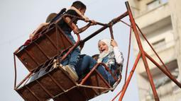 Anak-anak Suriah bermain di taman darurat selama perayaan Idul Fitri, hari libur Muslim yang dimulai pada akhir bulan puasa Ramadan, di Binnish di provinsi Idlib, Suriah barat laut yang dikuasai pemberontak, (26/5/2020). (AFP Photo/Omar Haj Kadour)