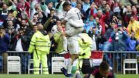 Dua pemain Real Madrid, Cristiano Ronaldo dan Lucas Vazquez, merayakan gol ke gawang Valencia pada laga La Liga di Santiago Bernabeu, Madrid, Minggu (8/5/2016). (AFP/Javier Soriano)