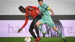 Duel Koscielny dengan Ismaila Sarr pada leg 1, babak 16 besar Liga Europa yang berlangsung di Stadion Roazhon Park, Rennes, Jumat (8/3). Arsenal kalah 1-3 kontra Rennes. (AFP/Damien Meyer)