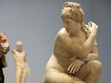 Seorang pegawai museum melihat ke arah patung marmer Crouching Venus, Romawi, abad ke-2 M, saat jumpa pers di The British Museum di London, Senin, (24/8/2020). Rute satu arah baru mengitari galeri Lantai Dasar akan memungkinkan pengunjung mengakses ribuan objek. (AP Photo/Kirsty Wigglesworth)