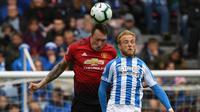 Bek Manchester United, Phil Jones, duel udara dengan pemain Huddersfield Town, Alex Pritchard, pada laga Premier League di Stadion John Smith, Minggu (5/5). Kedua tim bermain imbang 1-1. (AFP/Paul Ellis)