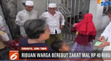 Ribuan warga berebut mendapatkan zakat sebesar Rp 40 ribu dari seorang pengusaha tekstil di Surabaya, Jawa Timur.