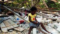 Seorang anak bermain di dekat rumahnya yang ambruk akibat guncangan gempa berkekuatan 7,1 SR di Kampung Kainui I, Distrik Angkaisera, Kepulauan Yapen, Papua, Jumat (25/6).(Antara)