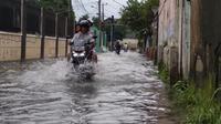 Warga berjalan menerobos banjir setinggi satu meter di Perumahan Rawalumbu Utara BBU Pasar Burung, Kota Bekasi. (Liputan6.com/Bam Sinulingga)