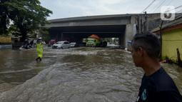 Petugas kepolisian mengatur lalu lintas saat banjir di Jalan Husein Nastranegara Perapatan Rawa Bokor, Tangerang, Sabtu (1/2/2020). Hujan deras yang mengguyur sejak Jumat (31/1) malam menyebabkan sejumlah kawasan di Tangerang terandam air. (merdeka.com/Imam Buhori)