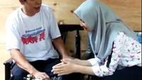 Masayu Nur Kautsar, murid SMP Nasima Semarang tengah menguji coba tongkat tuna netra ber-GPS kepada salah seorang penyandang tunanetra. (foto: Liputan6.com / suaramerdeka.com)