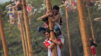 Peserta mengikuti panjat pinang kolosal dalam rangka merayakan HUT ke-74 Kemerdekaan RI di Pantai Ancol, Jakarta, Sabtu (17/8/2019). Sebanyak 174 batang pinang dengan beragam hadiah disediakan dalam lomba yang diikuti ratusan warga itu. (Liputan6.com/Faizal Fanani)